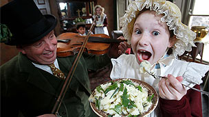 A young girl dressed in a bonnet and Victorian dress is eating mash while a man in a top hat plays a fiddle.