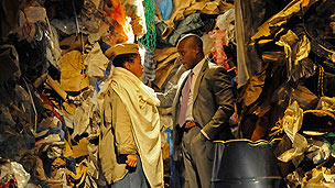A man and a woman acting, talking to eachother with a background of a rubbish tip.