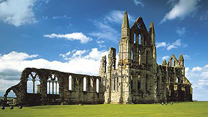 A larged, ruined abbey. With a blue sky and green grass