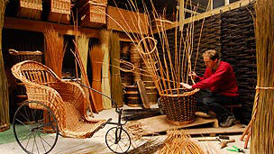 A large wicker chair on the left and a man weaving a willow chair on the right