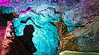 The interior of Wookey Hole Caves, lit with multicoloured lights of purple and greens.