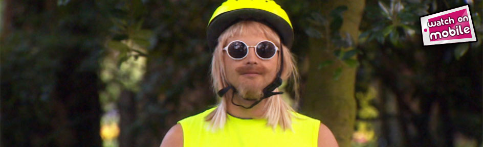 Mark Rhodes wears a cycle helmet, sunglasses, blonde wig and a high-vis vest. Watch on Mobile icon in corner.