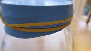 An elastic band around the ballon and jar