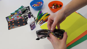White glue and a sweet decoration being stuck on some sunglasses