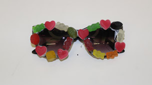 A finished pair of decorated sunglasses decorated with sweets