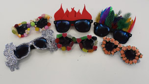 Lots of sunglasses decorated with lots of different decorations.