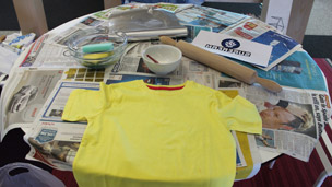 t-shirt and making materials on a table covered in newspaper