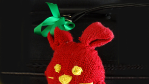 A red toy with a green ribbon attached