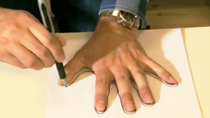 Barney Harwood drawing around his hand on a piece of paper