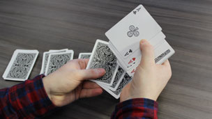 Hands shuffling a pack of cards to reveal four upturned aces