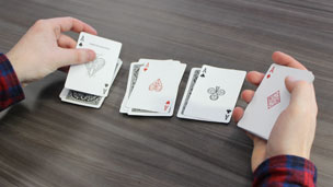 Dealing four aces onto four packets of playing cards