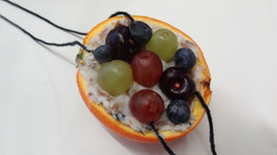 Mixture placed inside the orange half, with fruit decoration.