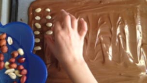 adding nuts to the melted slab of chocolate.