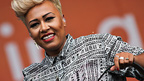 Emeli Sande performs on stage on blue background
