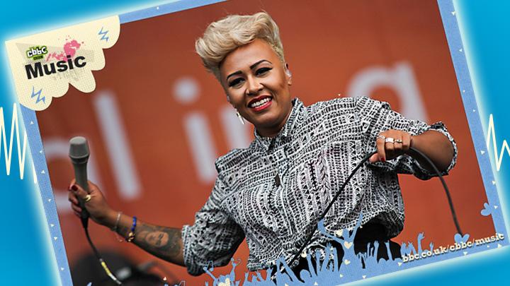 Emeli Sande performs on stage on blue background