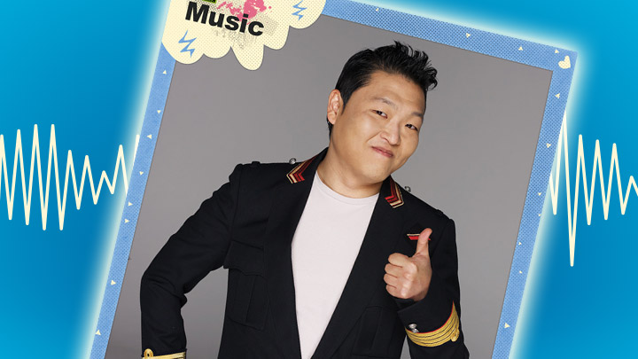 Psy looking at camera with a thumbs up. Blue background