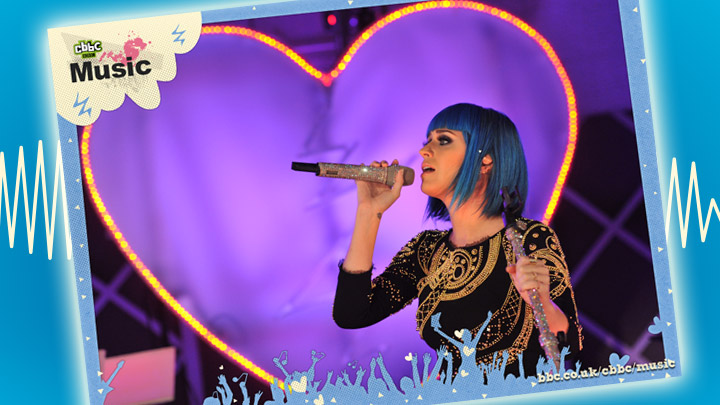 Katy Perry singing into a microphone. There is a giant loveheart behind her.