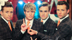McFly standing in line spelling 'Love' with their hands