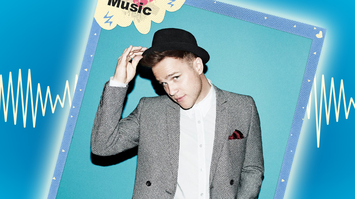 Olly looks to camera tipping his icon hat on blue background