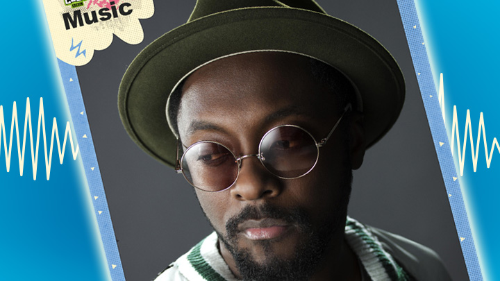 Will.I.Am looking to camera wearing a hat and round glasses
