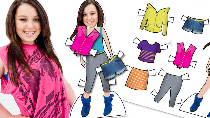 Dani Harmer standing next to her cut out doll and cut out clothes.