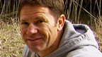 Steve Backshall with a red wolf in a cage.