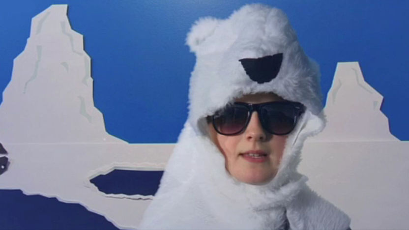 A Child dressed as a polar bear with an animated background.