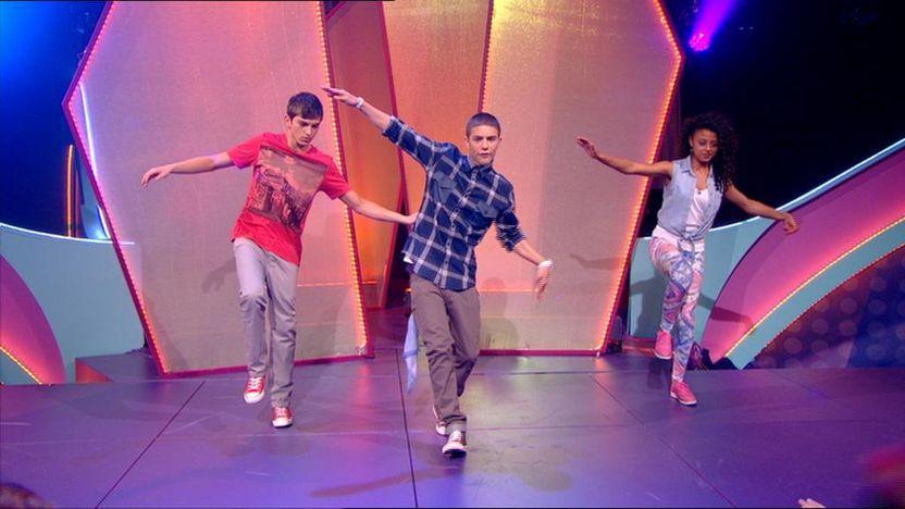 Aidan Davis dancing on stage with Richard Wisker and Talia