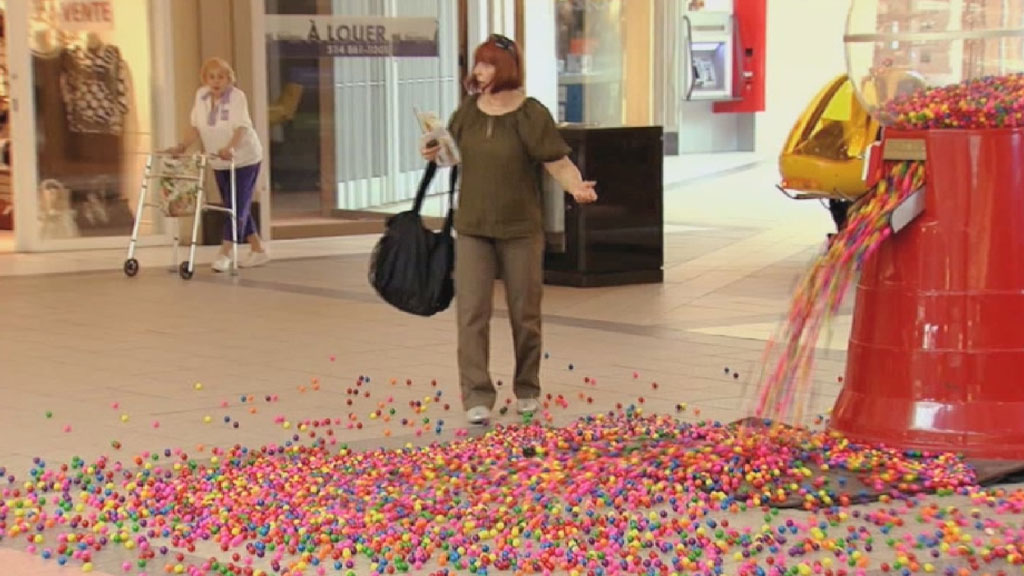 Woman stood beside faulty bubblegum machine.