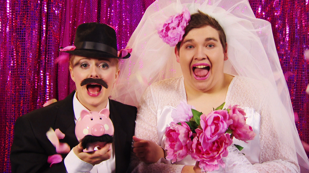 CBBC Office presenters Chris and Katie dressed as a married couple, hilariously though, Chris is the lipsticked bride and Katie is the moustachioed groom.