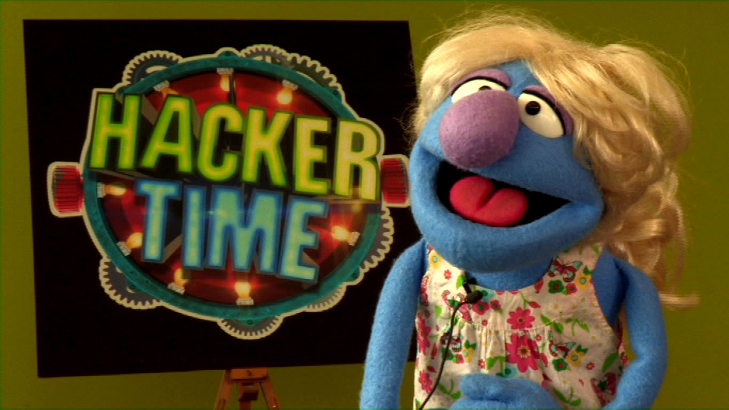 Lolly looks to camera infront of the Hacker Time logo
