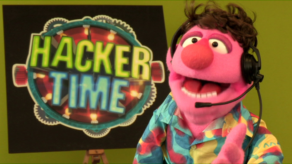 Herman looks to camera infront of the Hacker Time logo