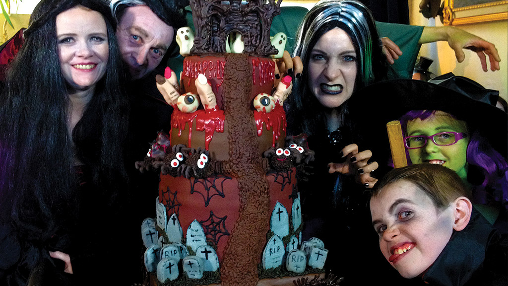 A family dressed up in halloween costumes with a gory cake.