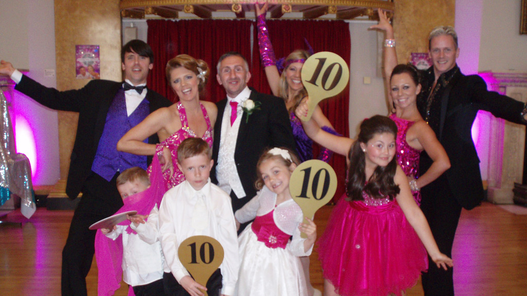 A family holding Strictly Come Dancing score boards.