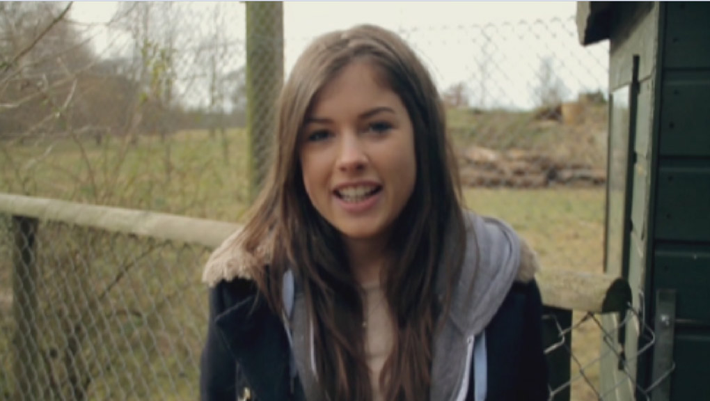 Aimee from Wolfblood standing outside a wolf sanctuary.