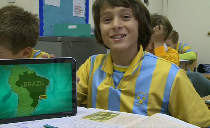 Andre with a tablet next to a map of Brazil.