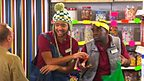 Johnny and Inel behind a shop counter, rapping about groceries.