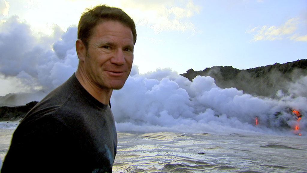 Steve Backshall from Deadly Pole to Pole with lava behind him.