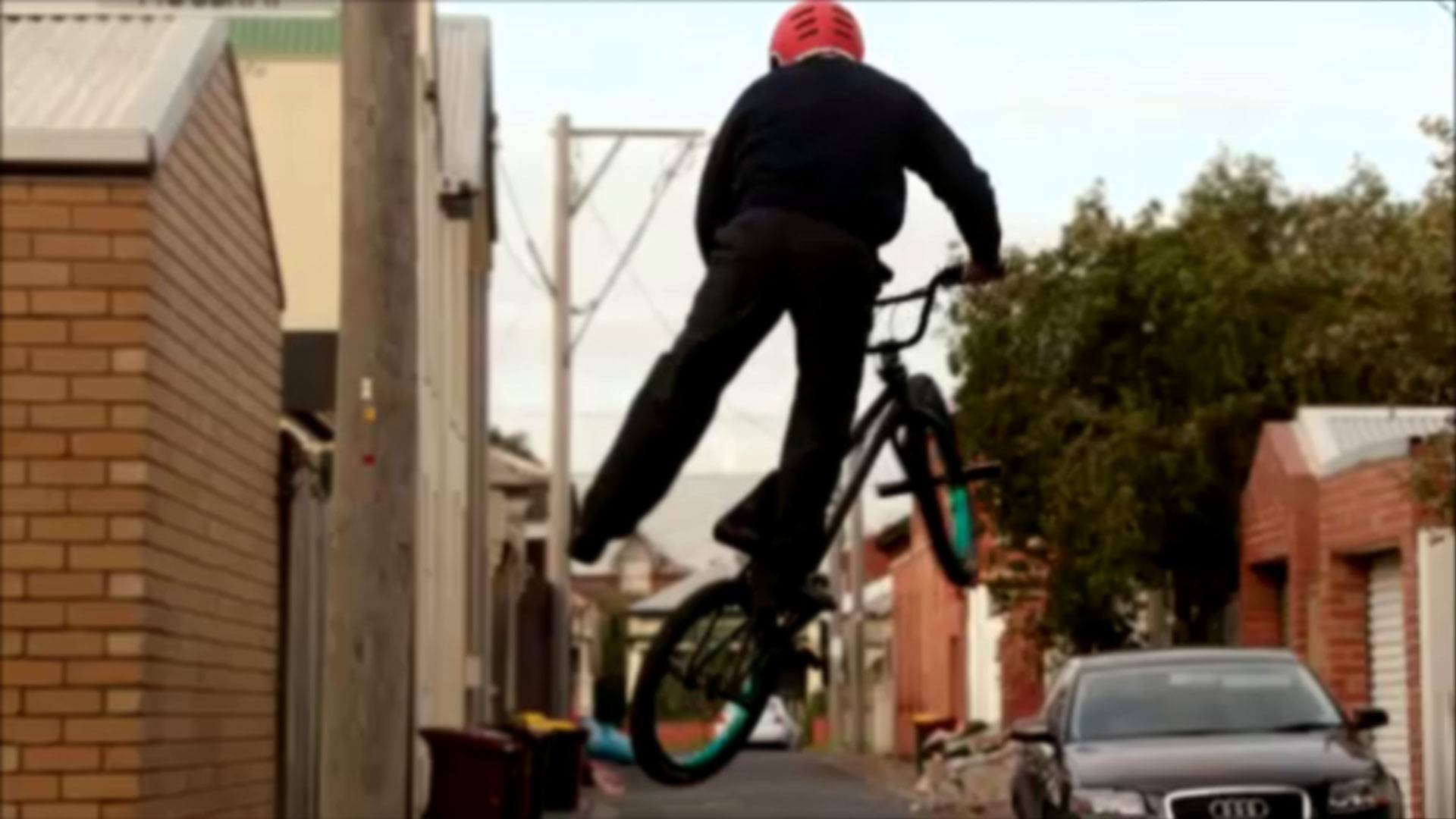 Stunt person jumps high on a bike.