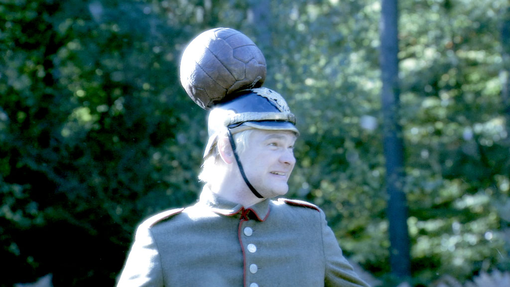 A German soldier with a football stuck to his helmet.
