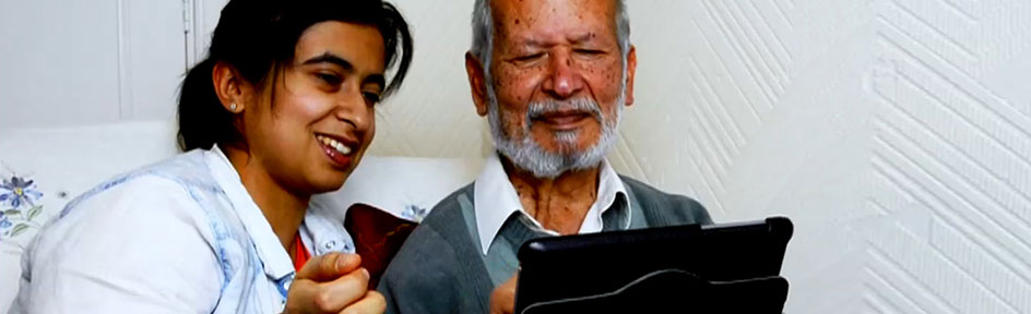 Sameena with an elderly man holding a tablet device