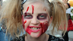 A girl in Halloween face paint.