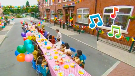 Children sat around a long table having a street party