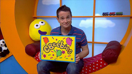CBeebies presenter Alex holding a birthday card
