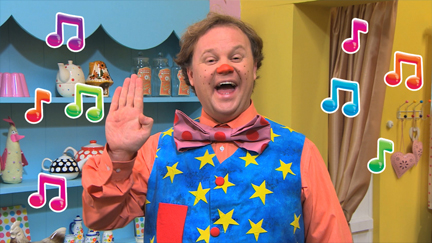Mr Tumble is waving.