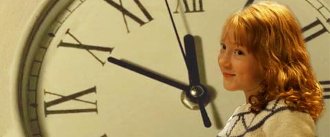 Katie Morag in front of a clock.