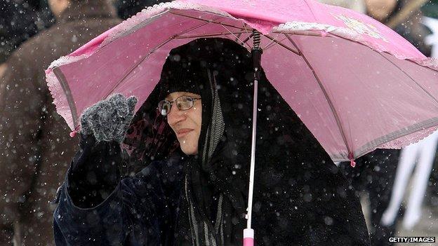 An Iranian woman holds an umbrella