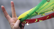 A protestor holds foulards in the colors of the Kurdish flag in her hand and forms the victory sign