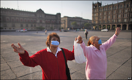 Women wearing surgical masks pray at the normally busy Zocalo central square in Mexico City