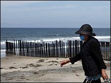 Una mujer camina cerca de la frontera entre EE.UU. y México